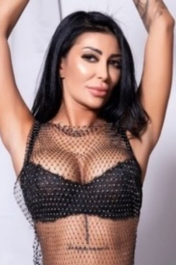 Arabella wearing a sexy mesh top over her black bra showing big boobs with hands above head.