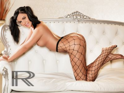 Eve bent over on her sofa wearing fishnets